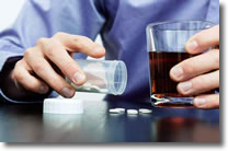 Person with glass of alcohol and pills on table